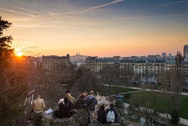 Students watching the sunset at Parc des Buttes-Chaumont in Paris.