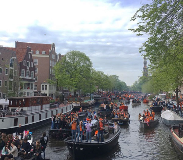 People celebrating in the canals of Amsterdam on King's Day.