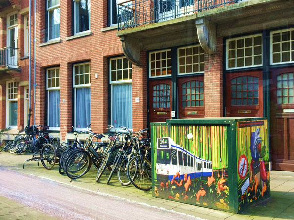 Bikes parked next to street art depicting a tram
